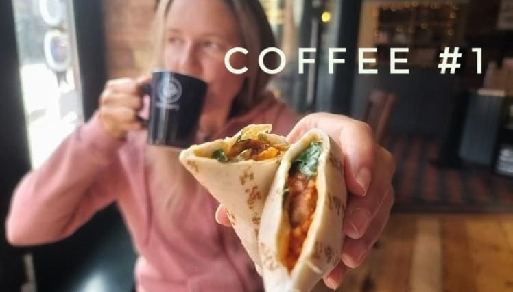 woman holding coffee and wrap